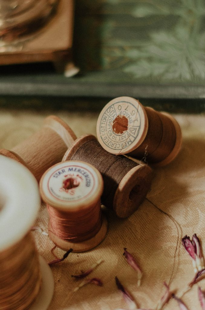 spools with threads on beige surface